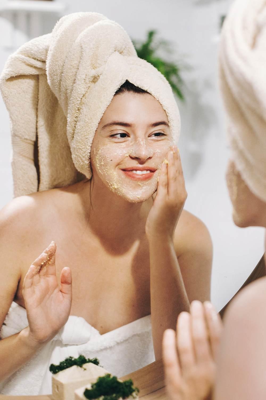 Exfoliante facial: Foto de mujer exfoliándose la cara.